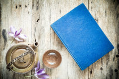 Teapot And Blue Book On Old Wooden Background Royalty Free Stock Photos