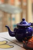 Teapot and ashtray. Blue teapot and ashtray on the table Royalty Free Stock Images