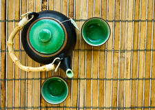 Teapot on bamboo mat Stock Images