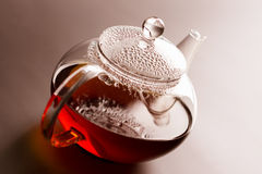 Teapot with black tea Stock Photos