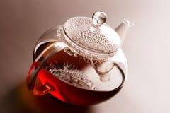 Teapot with black tea Stock Photos