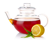 Teapot with black tea, green leaves and lemon. Slices  on white background Royalty Free Stock Photography