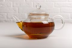 Teapot with black tea. Kettle with hot black tea in front of a white wall stock images