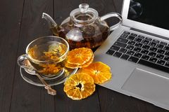 Teapot with black tea, roses, oranges and grapefruit on light ba. Ckground Stock Images
