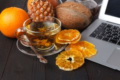 Teapot with black tea, roses, oranges and grapefruit on light ba. Ckground Stock Image