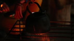 Teapot boiling on flames and burning wood logs in the desert at night. stock video