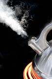 Teapot with boiling water Stock Images