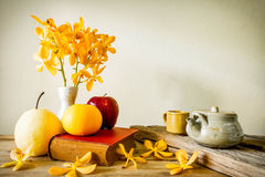 Teapot, Books and flower with fruit, home decoration concept Royalty Free Stock Images