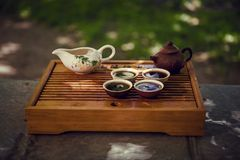 Teapot, bowl and four cups. Drinking Puer tea in nature. stock photography