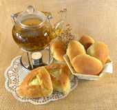 Teapot with buns and candle Stock Images
