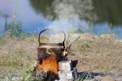 Teapot on campfires amongst stone. Space for text. Teapot on campfires amongst stone stock image