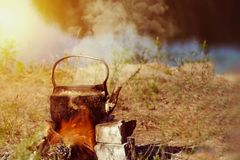 Teapot on campfires amongst stone. Space for text. Teapot on campfires amongst stone stock photography