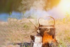 Teapot on campfires amongst stone. Space for text. Teapot on campfires amongst stone stock images