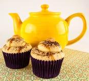 Teapot and caramel cupcakes Stock Image