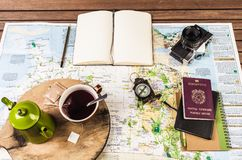 Teapot, compass, passport, photo camera and block notes on map Royalty Free Stock Photo
