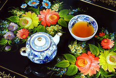 Teapot and cup. Teapot with flowers art in the background Stock Images