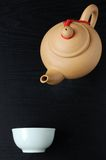 Teapot and cup. Yellow teapot and cup on black background Stock Images