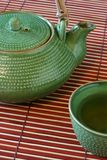 Teapot and cup. On bamboo mat Royalty Free Stock Photography