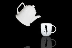 Teapot and cup with black isolated. Isolated of white teapot and cup with black background Royalty Free Stock Image