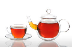 Teapot and cup with black tea Stock Photos