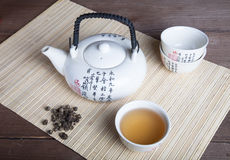 Teapot, cup of green tea and tea leaves on a napkin from a bambo Royalty Free Stock Photography
