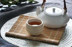 Teapot with a Cup of Hot Tea. On bamboo mat stock photo