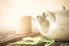 Teapot and cup on old wood table, vintage style. Royalty Free Stock Photography