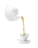 Teapot and cup. Pouring tea in tea cup. Teapot and cup isolated on white background Stock Photos