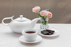 Teapot, cup, roses, and chocolate on a plate Royalty Free Stock Images