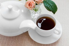 Teapot, cup, and  roses on a plate Stock Photos