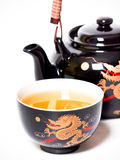 Teapot with cup of tea. Black teapot with cup of tea Royalty Free Stock Photos