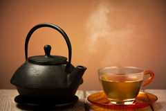 Teapot and a cup of tea. On an old wooden table - hot steam smoking from cup of tea Stock Image