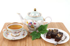 Teapot and cup of tea with brownies. Teapot and cup of tea with 3 brownies on white background Stock Photography