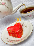 Teapot, cup of tea and cake in form of a heart. Cup of tea and Valentine strawberry cake in form of a heart Stock Image