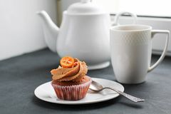 A teapot, a cup of tea and a caramel cupcake. Stock Photos