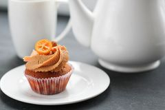 A teapot, a cup of tea and a caramel cupcake. Royalty Free Stock Photos