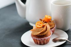A teapot, a cup of tea and a caramel cupcake. Stock Photography