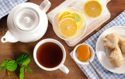 Teapot and cup of tea with lemon, ginger and mint Royalty Free Stock Image