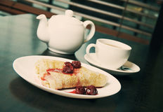 Teapot, cup of tea and pancakes with cherry confiture Stock Photo