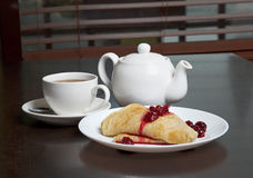 Teapot, cup of tea and pancakes with cherry confiture Stock Image