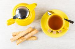 Teapot, cup of tea, spoon, sugar and flaky sticks Stock Image