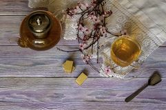 A teapot, a cup of tea and waffles on a wooden table royalty free stock image