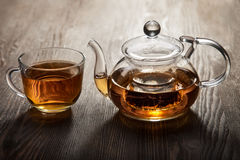 Teapot and cup of tea on wooden table Stock Images