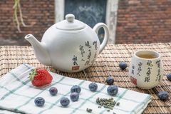 Teapot with cup of tea on the woven mat with blueberries and strawberry Royalty Free Stock Photo
