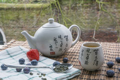 Teapot with cup of tea on the woven mat with some blueberries, strawberry and teaspoon on towel. Teapot with cup of tea on the woven mat with some blueberries Royalty Free Stock Photos