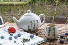 Teapot with cup of tea on the woven mat with some blueberries and strawberry on towel. Teapot with cup of tea on the woven mat with some blueberries and Stock Photography