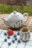 Teapot with cup of tea on the woven mat and white towel with blueberries and strawberry Royalty Free Stock Image