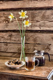 Teapot, cup of tee, plate with cookies and a vase with daffodil flowers  on a table against the background of the wooden walls. Teapot, cup of tee, plate with Royalty Free Stock Photography