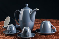 Teapot and cups. Closeup of retro style teapot and cups arranged on table with black background stock photography