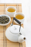 Teapot and cups of green tea on a wicker mat, top view Royalty Free Stock Photography